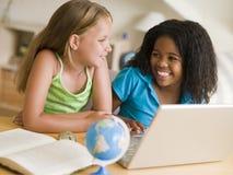 执行女孩家庭作业膝上型计算机他们的二个年轻人 库存照片