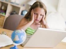 执行女孩家庭作业膝上型计算机年轻人 免版税库存照片