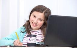执行女孩少年她的家庭作业 图库摄影