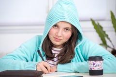 执行女孩少年她的家庭作业 库存照片
