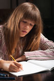 执行女孩少年她的家庭作业 库存图片