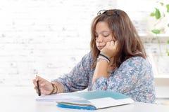 执行女孩少年她的家庭作业 免版税库存照片