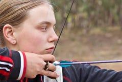 执行女孩的射箭少年 免版税图库摄影