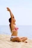 执行她舒展的女子瑜伽的胳膊 库存图片