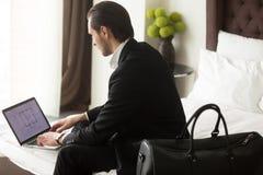 执行委员在旅馆里检查在膝上型计算机的庄园计划 图库摄影