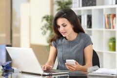 执行委员在网上与膝上型计算机和电话一起使用 免版税库存图片