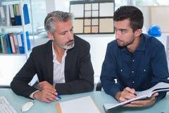 执行委员谈话与工作者在办公室 库存照片