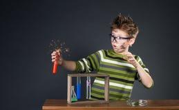 执行实验的小男孩。疯狂的科学家。 免版税库存图片