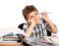 执行家庭作业勉强男小学生 免版税库存图片