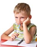 执行家庭作业哀伤的男小学生 库存图片