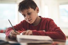 执行家庭作业学校的男孩 库存图片