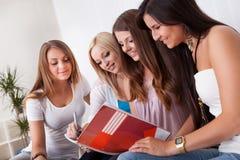 执行家庭作业的四个女学生 免版税库存图片