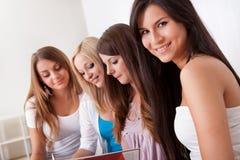 执行家庭作业的四个女学生 免版税库存照片