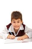执行家庭作业的微笑的男孩 免版税库存图片
