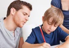 执行家庭作业的新男孩 免版税图库摄影