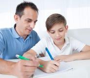 执行家庭作业的父亲和儿子纵向  免版税库存图片