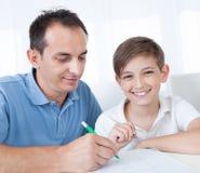 执行家庭作业的父亲和儿子纵向 库存图片