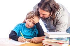 执行家庭作业的父亲和儿子 库存照片