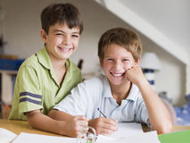 执行家庭作业的男孩他们的一起二个年轻人 免版税库存图片