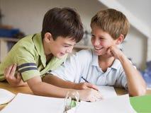 执行家庭作业的男孩他们的一起二个年轻人 库存照片