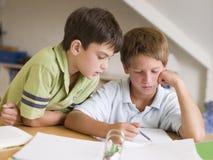 执行家庭作业的男孩他们的一起二个年轻人 库存图片