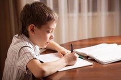 执行家庭作业的男孩 库存照片