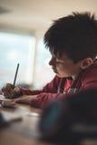执行家庭作业的男孩 免版税库存照片