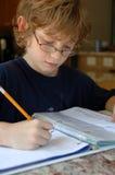 执行家庭作业的男孩 免版税库存图片