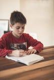 执行家庭作业年轻人的男孩 库存照片