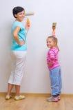 执行家庭维修服务的妇女和她的女儿 库存照片