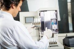 执行尿液分析的技术员在实验室 免版税库存照片