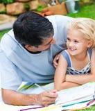 执行庭院家庭作业的爸爸女儿 库存照片