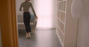 执行当代舞蹈的嫩白种人芭蕾舞团首席女演员下来坐沙发并且在光和舒适室放松 股票录像