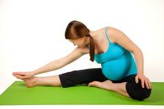 执行怀孕的少妇舒展和。 库存照片