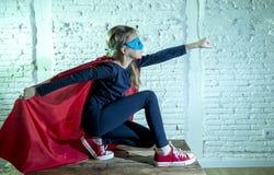 执行愉快和激动的摆在的佩带的盖帽和面具的女孩7或8岁女孩在特级英雄幻想服装lo 免版税库存图片