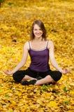 执行执行公园女子瑜伽的秋天 免版税库存照片