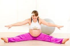 执行执行怀孕的微笑的舒展的妇女 库存照片