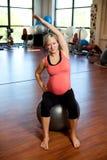 执行执行怀孕的舒展的妇女 免版税库存图片