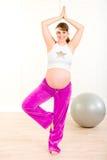 执行执行pilates怀孕的微笑的妇女 免版税库存照片