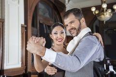 执行探戈的愉快的男人和妇女画象在餐馆 免版税库存图片
