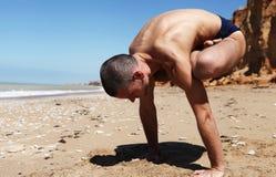 执行摆锤瑜伽姿势的人 免版税库存图片