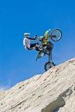 执行摩托车骑士自行车前轮离地平衡特技 免版税库存照片