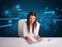 执行文书工作有未来派背景的女实业家 免版税图库摄影