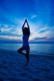 执行日落女子瑜伽的海滩 免版税库存图片
