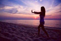 执行日落女子瑜伽的海滩 库存图片