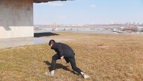 执行杂技把戏和轻碰在草的黑色衣服的一年轻人 股票录像