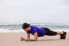 执行板条锻炼的女运动员 免版税库存图片