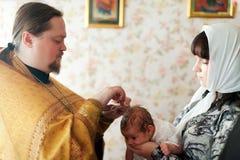 执行洗礼仪式仪式的教士 免版税库存照片