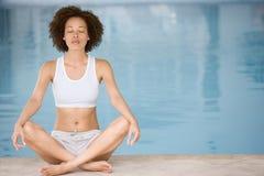 执行游泳池边坐的女子瑜伽 免版税库存图片