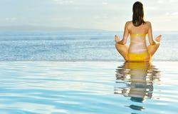 执行游泳池边女子瑜伽 免版税库存照片